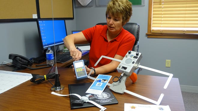 Detective Nancy Wilt, of the Coshocton County Sheriff's Office, demonstrates a tracking system used to find people suffering from Alzheimer's disease or similar disorders who wander from home.