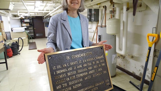 Birchard Library Director Pam Hoesman holds the marker honoring British soldiers who died in battle in Fremont in 1813.