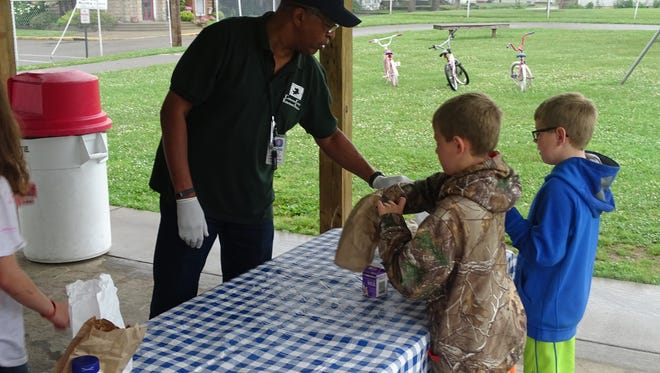 William Johnson, left, co-chairman of the Coshocton County Fatherhood Initiative, helped distribute free lunches to Coshocton Children at Himebaugh Park last summer. The program will resume Monday.through Aug. 19.