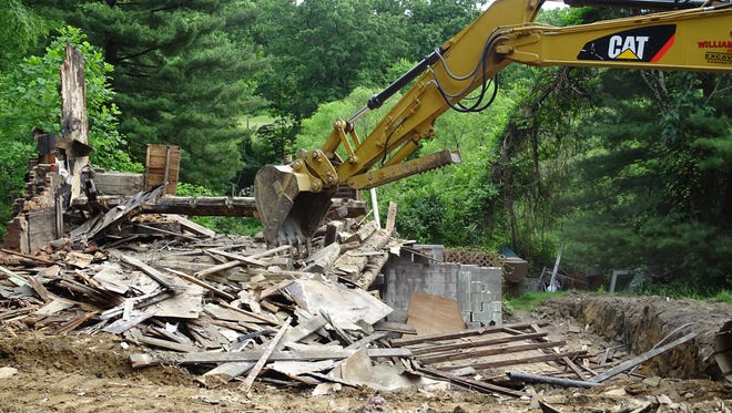 Workers use a backhoe to demolish a former log cabin on Township Road 285, west of Tyndal. The home was destroyed by fire last December. The owner plans to build a new house on the site.