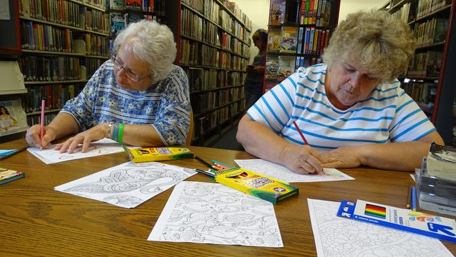 Kathy Metzger and Beverly Miley enjoy coloring at the Madison Branch of Mansfield/Richland County Public Library.