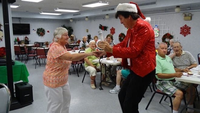 Brian Brenner, Elvis impersonator, dances and sings to holiday hits with Shirley Miller during a 'Christmas in July' party at Fort Stephenson House.
