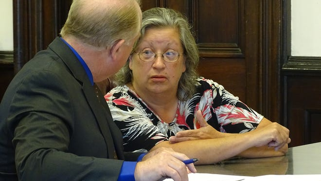 Former office manager Linda L. Vollene, of New Concord, consults with Public Defender Jeff Mullen before pleading guilty to grand theft and other felony charges Tuesday in Coshocton County Common Pleas Court..