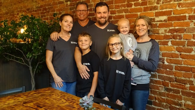 Cody and Danyelle Rutherford (center and right) along with their children Bayla, Conner and Caryline stand with Sheri and Ronnie Rutherford in the R Kitchen on Paint, just days before the grand opening. Cody Rutherford, owner, will be the restaurant's chef.