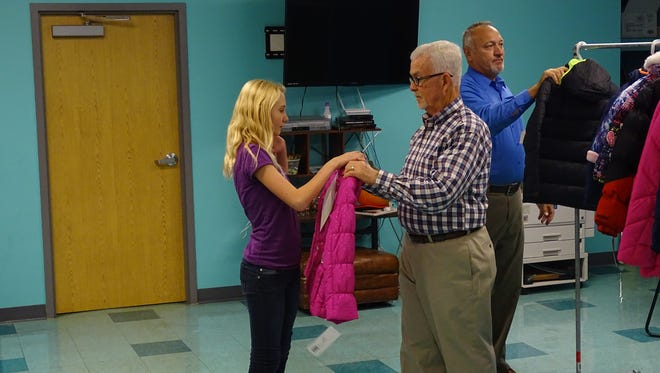 Bob LaPrad, chair of the coats for kids program for the Knights Columbus Council 505 of Zanesville, hands Hannah Sartin a winter coat at Eastside Community Ministry Wednesday.