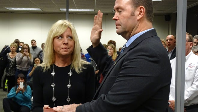 Sandusky County Sheriff-elect Chris Hilton is sworn in Thursday. His wife Rebecca holds the Bible. Hilton said the room full of family, friends and county residents made him excited to get started as sheriff. Hilton's four-year term begins Jan. 1.