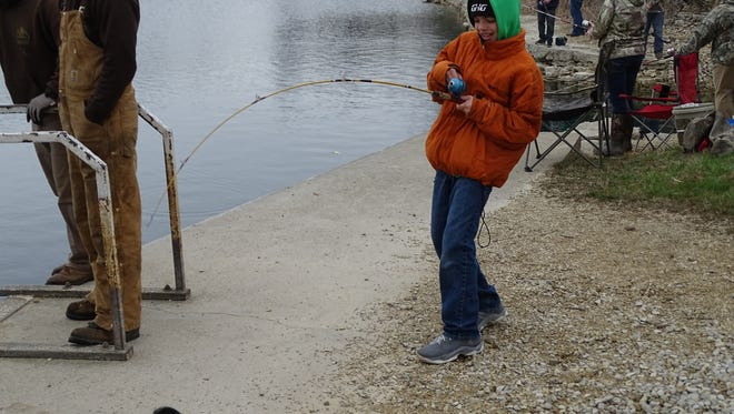 Carson Miller reels in a rainbow trout at White Star Quarry on Thursday after the state released 1,513 rainbow trout. All anglers must have a fishing license, and are allowed to catch and keep up to five fish per day.