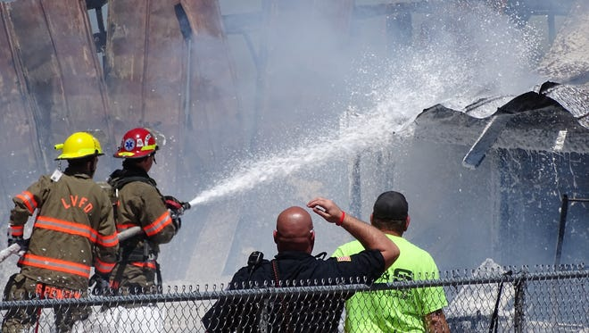 Firefighters work to extinguish flames at a barn fire on Hayes Avenue in Washington Township.
