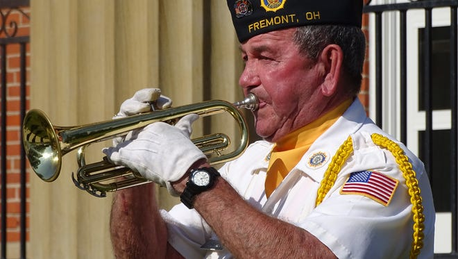 """Bugler Dana Dorsey played """"Taps"""" in front of the Sandusky County Courthouse during a previous Memorial Day ceremony, as the community honored fallen veterans."""