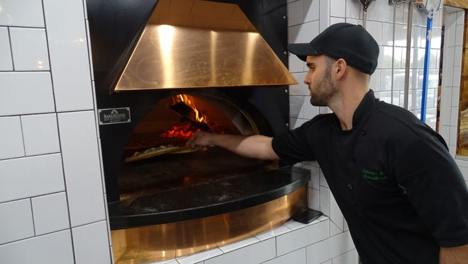 Anthony Russo slides a pizza into the wood-fire oven. Each pizza takes about three minutes to cook.