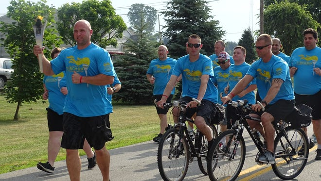 Fremont Police officer Brian Kingsborough holds the torch as he leads the 2017 Special Olympics Ohio Law Enforcement Torch Run through Fremont on Thursday.