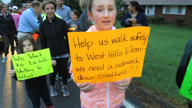 Emily Ernst holds up a sign in support of a sidewalk for West Hills' Sheffield Drive.