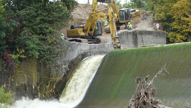 Workers begin notching the Ballville Dam on Wednesday as the city takes the next step toward the dam's scheduled demolition in 2018.