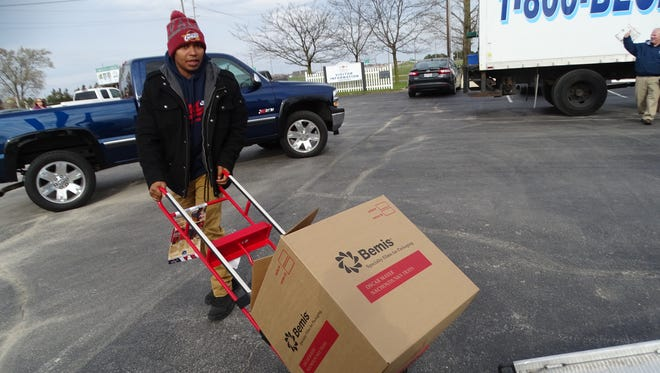 Tim Freeman of Tim's Neighborhood Bar Grill loads a box of food onto a truck to be donated to local families in need.