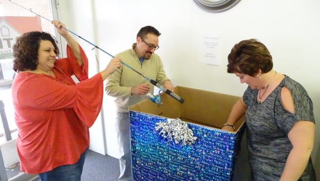 """From left, Vicki Schmitz, Mike Dziak and Monica Camarata look at some of the toys donated at Bolte Real Estate's collection box Monday in Clyde. The real estate office is one of four collection sites for the annual """"Caring for Clyde Kids"""" Community Toy Collection, which is accepting donations through Dec. 13."""