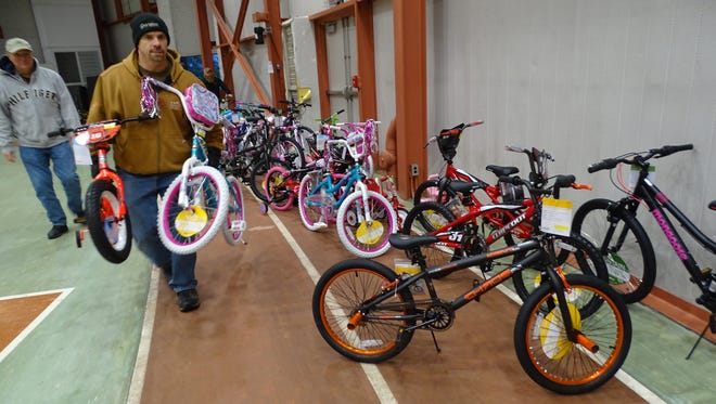 Eddie Hatfield, who started the bike donation program with his colleagues at Whirlpool Corp. three years ago, carries 2 of the 36 bicycles that will be given away Wednesday through the Toys for Tots program.