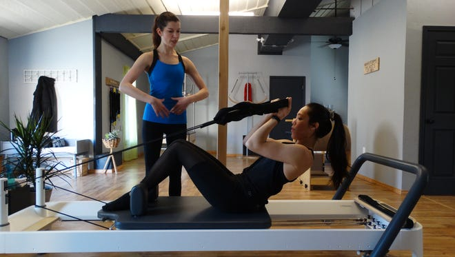 Waveforms Pilates owner/instructor Courtney Holcomb works with student Nalani Andres in the business' new Neenah studio.