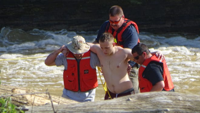 Members of the Ballville Volunteer Fire Department's Water Rescue team help this unidentified swimmer out of the water Monday near the Ballville Dam after he and three others were swept up in the Sandusky River's current. The swimmer was transported to the hospital by Sandusky County EMS.