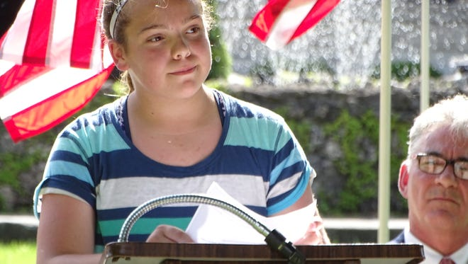 """Sara Gross, a fifth grade student at Stamm Elementary School, reads her essay """"Why Our Veterans Are America's Heroes"""" at the Elks Lodge 769 Flag Day Ceremony in Fremont's Flag Park."""