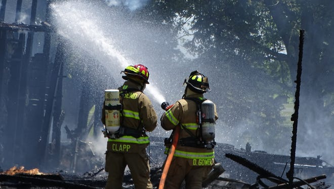 Firefighters sprayed water on a fire at a home in the 3600 block of Sandusky County Road 231 Friday. No one was injured in the fire, which occurred around 1 p.m.