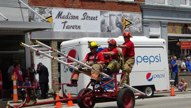 Three firefighters from the Polk Jackson Perry Fire Department balance on a ladder during the NOVFA parade in Gibsonburg.