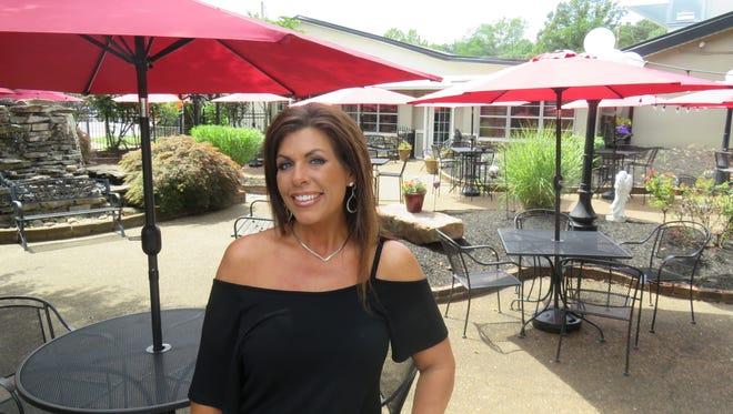 Merelli's Restaurant owner Misty Mills stands in courtyard patio.