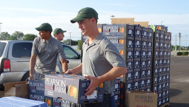 The Peach Truck workers gladly help carry boxes of peaches to customers' cars.