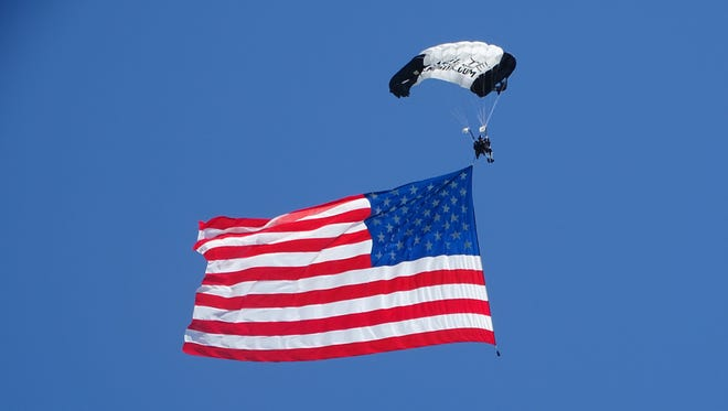 Sgt. First Class Dana Bowman parachutes from the sky, carrying with him a 2500 square foot American flag, at the First Shot Ceremony at Camp Perry.