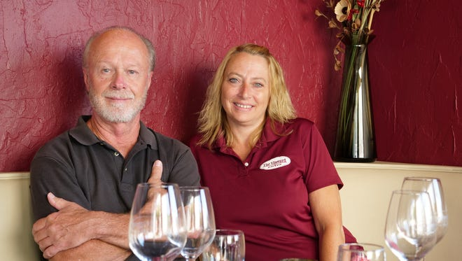 Vineyard Wine Bar owner Joe Lertch and general manager Nina Peery sit at one of the Rehoboth bistro's booths.