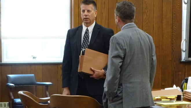 Former Sandusky County Sheriff's Detective Sean O'Connell, in dark suit, leaves Sandusky County Common Pleas Court after pleading guilty to felony tampering with evidence on July 30.