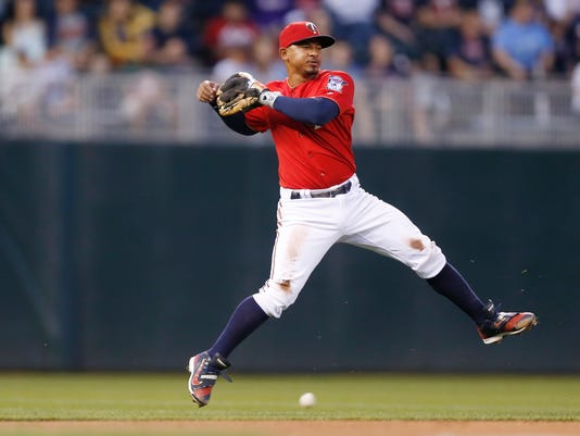 Minnesota Twins shortstop Eduardo Escobar makes a throwing motion minus the ball, on a single by Los Angeles Angels' Carlos Perez during the third inning of a baseball game Friday, April 15, 2016, in Minneapolis. (AP Photo/Jim Mone)