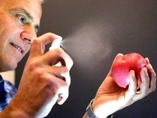 Anthony Zografos, founder and CEO of DNA Trek, sprays a solution on an apple that will allow reseachers to trace the apple back to its original source at Lawrence Livermore Laboratory in Livermore, Calif.