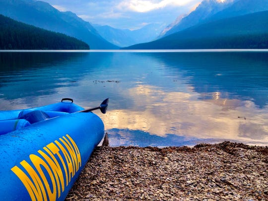 An infatable kayak sits on the beach of Bowman Lake.