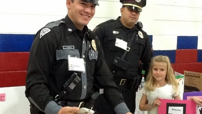 New Mexico State Police officers Jeff Perales and Kenneth Figueroa pose with a Chaparral Elementary School student.