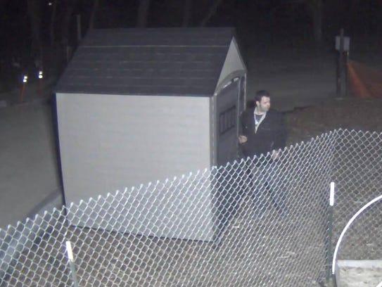 A surveillance image shows a man breaking into a garden