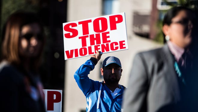A man holds up a sign during a vigil to end gun violence in downtown Phoenix on Dec. 13, 2015.