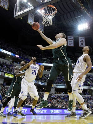 Michigan State's Matt Costello puts up a shot against Duke's Jahlil Okafor, right, during the first half Tuesday night.