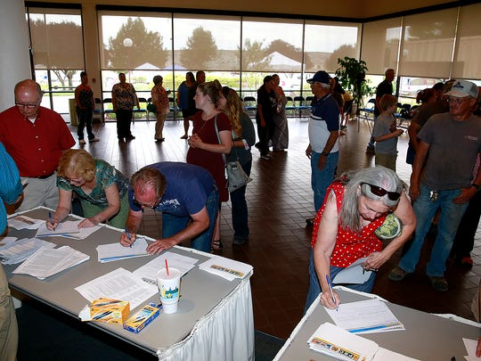 People line up to submit questions for officials of the New Mexico Public Regulation Commission, AV Water company and the New Mexico Environment Department before a public meeting on Thursday at the Farmington Civic Center.
