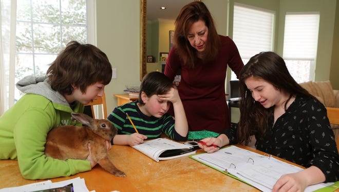 """Lisa Rudley from Briarcliff Manor is opting two of her kids out of the upcoming state exams. Here she is pictured at home with Max, 12 with bunny Harry, Derek, 10 and Lexi, 14 March 21, 2015. She is also the co-founder of the New York State Allies for Public Education which has started a campaign to purchase """"Refuse the Tests"""" ads on billboards placed strategically around the state opposing these tests."""