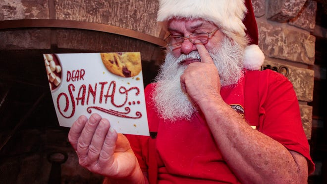 Sitting in front of the fireplace at his home near the North Pole, Santa Claus reads one of the thousands of postcards and letters he receives every years from children sharing their Christmas wishes.