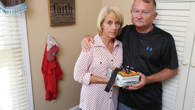 Karl Cooley, right, and his wife Brenda Cooley hold a stack of sympathy cards in a room where their son Adam died of a drug overdose.  They display a bible verse from Luke 1:37 and their son's cap and t-shirt on the wall.  The bible verse was a gift from their Nar-Anon support group. Apr. 20, 2017