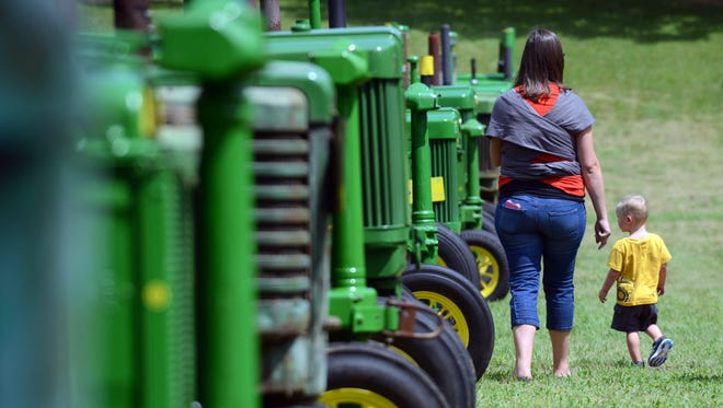 People walk down a row of antique John Deere tractors Friday, Aug. 19, 2016, at the Alley Park Antique Tractor Show in Lancaster. The show features more than 100 antique tractors, trucks and machinery as well as craft, food and parts vendors. The show runs through Sunday at Alley Park in Lancaster.