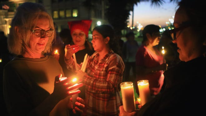Melissa Utter (left) helps light candles during a candlelight peaceful protest against President Donald Trump on Saturday, Jan. 21, 2017, in Corpus Christi.