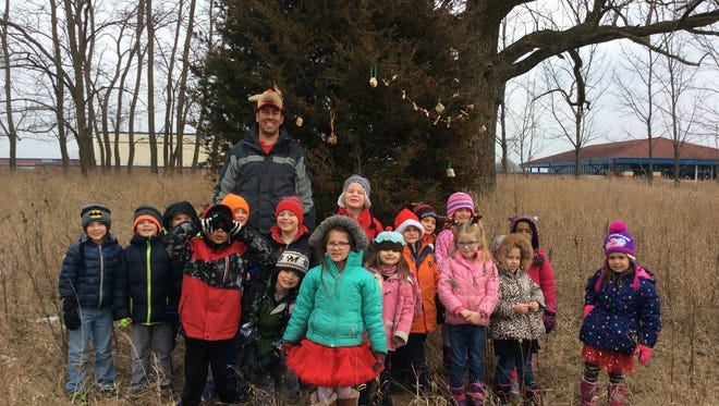 Peter Dargatz (back) and some students in his nature kindergarten class pose with a tree on the trail near the school they decorated during the holidays in Dec. 2017.
