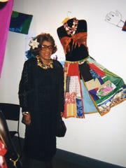 Cleota Wilbekin stands with one of her quilted dresses.