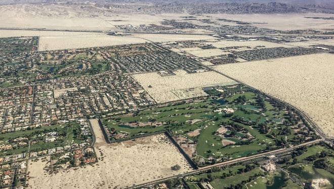 The green landscaping of subdivisions, golf courses and the Annenberg Retreat at Sunnylands border the desert in Rancho Mirage.