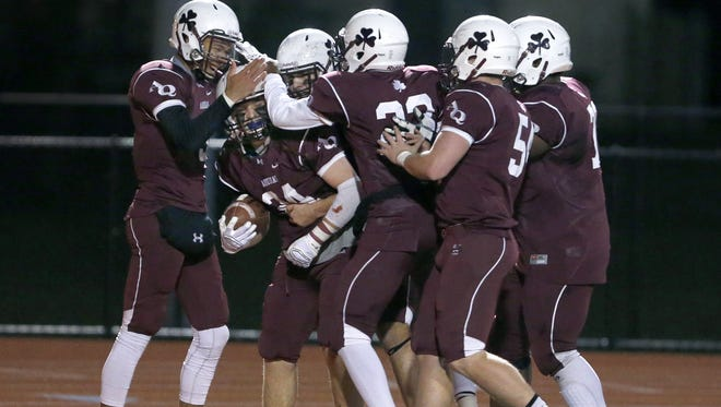 Aquinas teammates celebrate Tyler Olbrich's 34-yard touchdown reception, a screen pass he turned into a score against Liverpool, during the Class AA West state semifinal.
