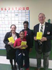 Renaissance Charter of St Lucie Principal Christiana Coburn and a third grade student receive the dictionaries from Port St Lucie Rotary Club members Dawn Bloomfield and George Mcilrath.
