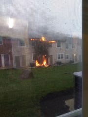 A fire rages as seen from a nearby apartment at Stoneybrook Apartment complex in Claymont, Del.