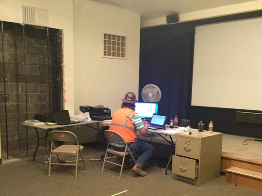 A construction supervisor works in a makeshift office in the Visitor Center's theater. At left is an opening in the wall where an emergency door will be placed.